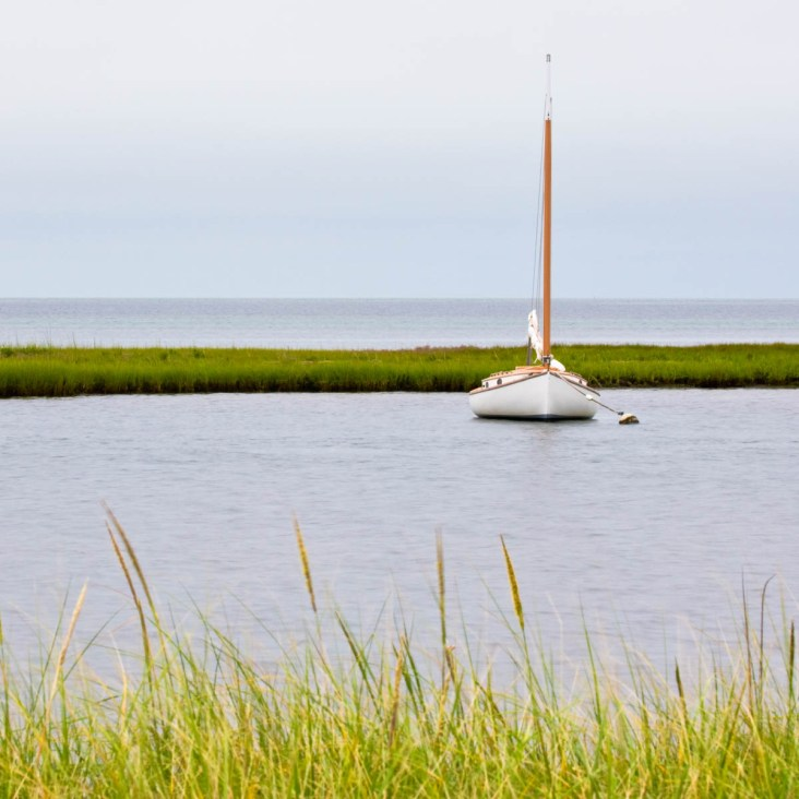 white catboat at anchor