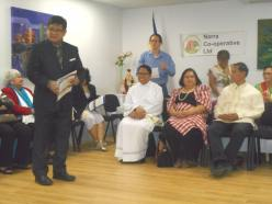 Councillor Rey Manoto standing, giving the Mayor's Speech to the members and guests, sitting L-R in centre, is Father Ferdinand de la Cruz, Mryna Lopez (wife of Dr. Lopez) and Dr. Jimmy Lopez, with emcee Charles Chan at the back (in blue).