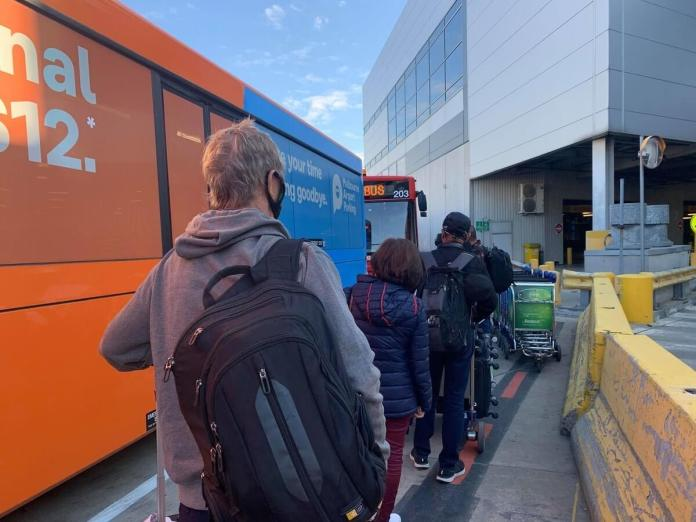Passengers who arrived in Melbourne queue up to board the SkyBus to take them to the hotel on a 14-day quarantine period. | Photo: Gayzha Davao
