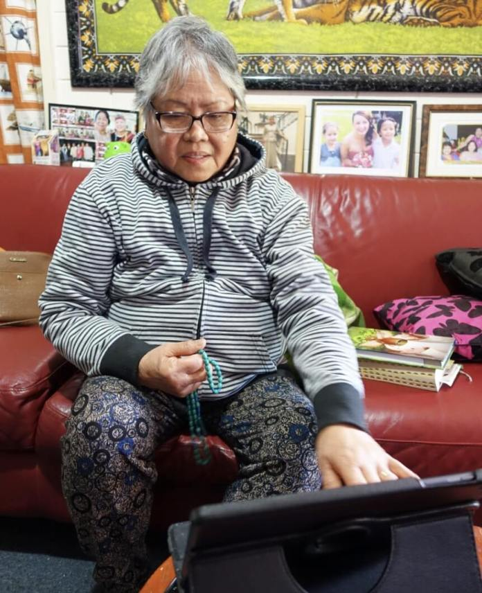 VIOLETA is a Charismatic Catholic and enjoys watching Mass via YouTube in the Philippines. She has her Bible and rosary beads with her. Often some of the other residents join her to attend Mass online. | Photo: Jason Cordi