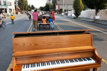 People try out the pianos put in the street by A-1 Piano.