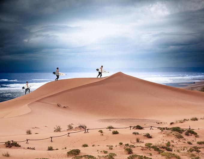 Three Teenage Boys Climbing Sand Dunes On The Way To Surf by Susan McKenzie