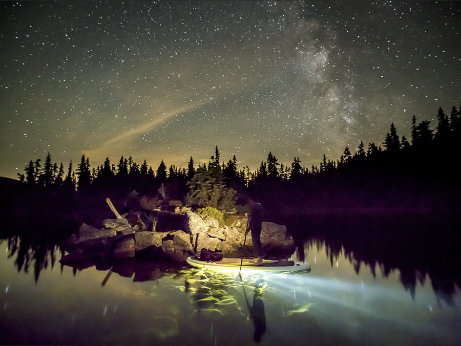 Paddleboarding at night on Callaghan Lake by Gerald Oskoboiny