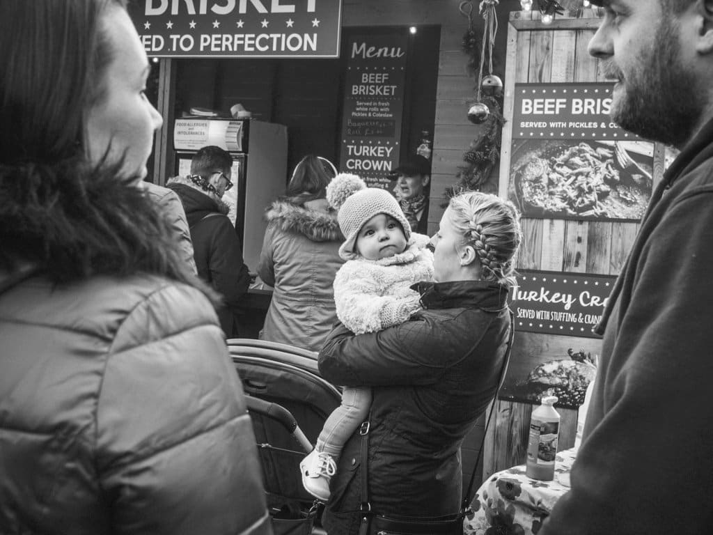 baby in mothers arms looking away