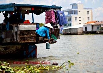 Een bootvrouw haalt water (foto: Pho Vietnam © Kim Le Cao)