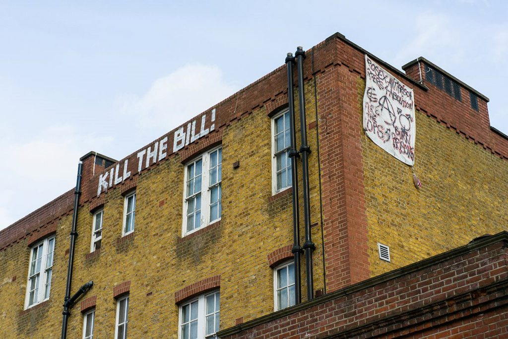 """The squatted ex-police station in Clapham, with """"kill the bill"""" painted at the top and a banner hanging from the roof."""