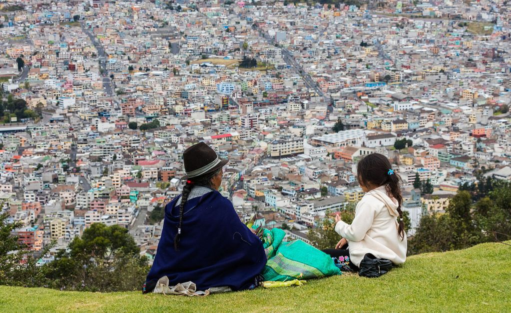 Two indigenous people looking out over a city in Ecuador