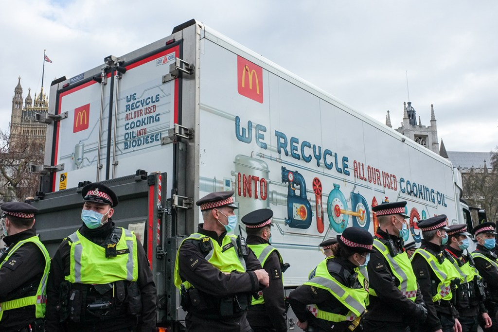 Metropolitan Police officers protect a McDonald's delivery lorry