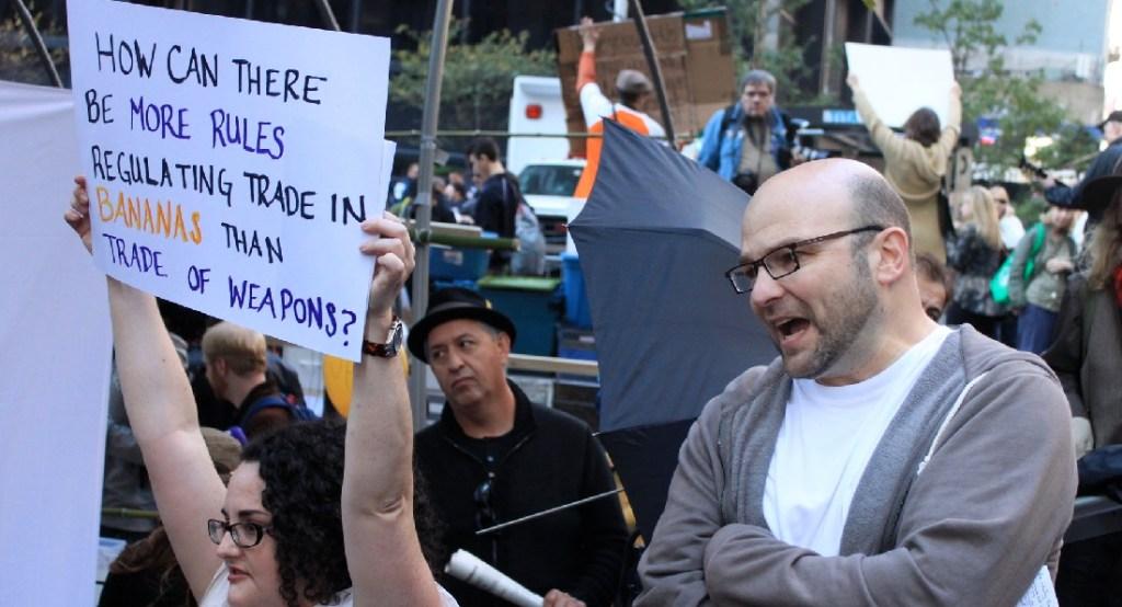 Andrew Feinstein speaking next to a banner