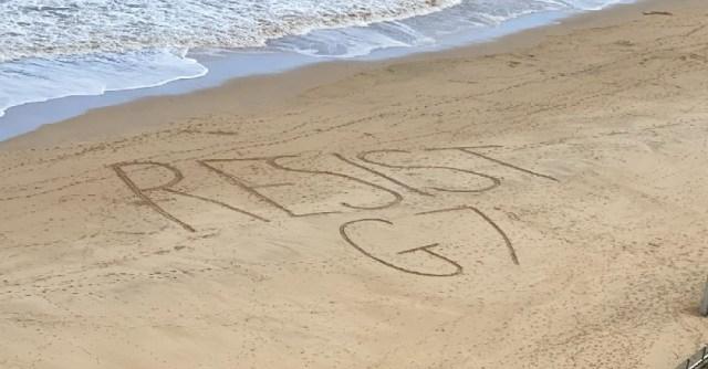 Resist G7 written on beach