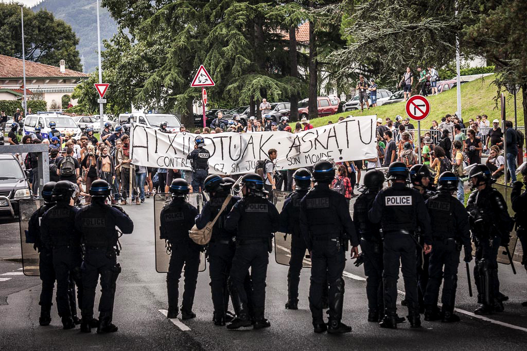 A line of police face protesters with a banner at the 2019 G7 summit in Biarritz, France.