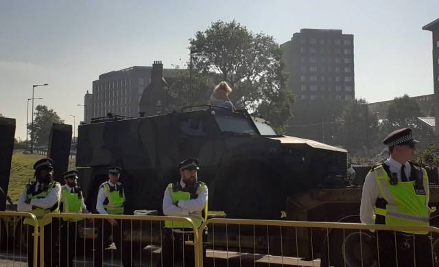 A protester sits on top of a military vehicle being taken into the DSEI arms fair in London as police stand guard