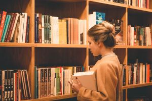 Image of a young blond caucasian woman in front of book shelves