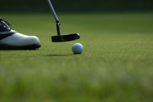 Photo of a golfer foot in a golf shoe with a putter and a golfball on a green