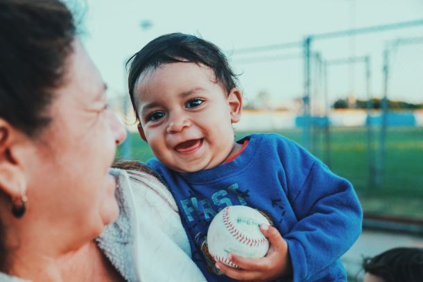 Person and infant with a baseball