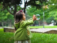Photo of young child in a green coat in the grass following a bubble
