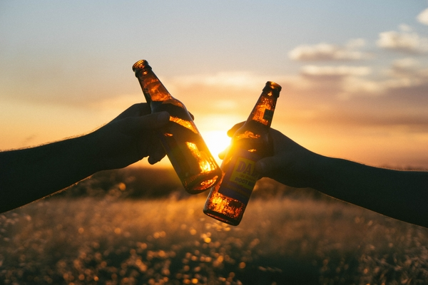 Image of two hands extending beer bottles toward each other with a sunset in the background