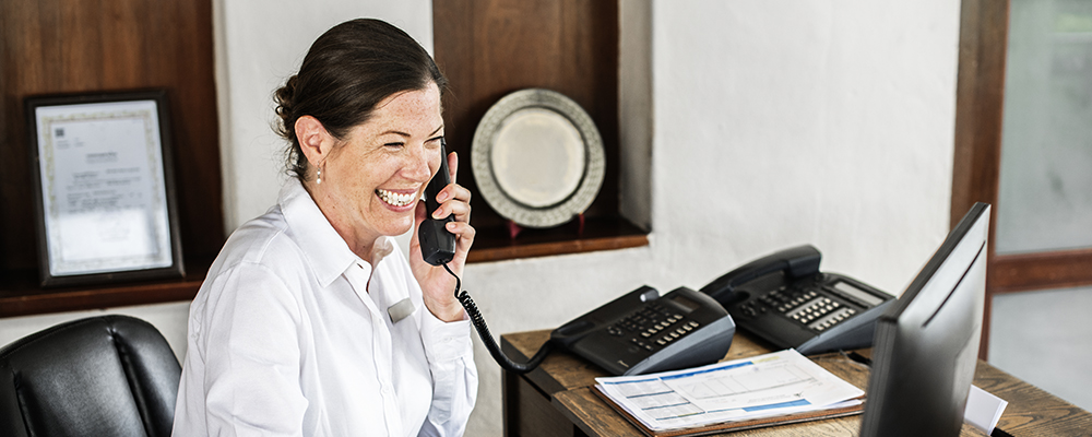 A woman answering a call at her desk