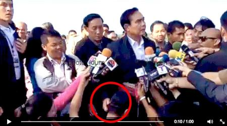 Thailand Prime Minister Prayut Chan-ocha scratches the ear of a Thai journalist squatting before him while conducting a media briefing.