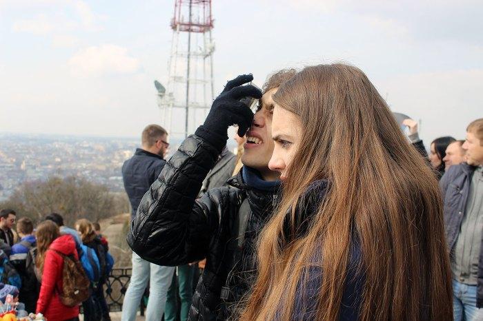 Пара спостерігає сонячне затемнення за допомогою задимленої скляної попільнички, Львів 20 березня 2015 року,оглядовий майданчик Високого Замку