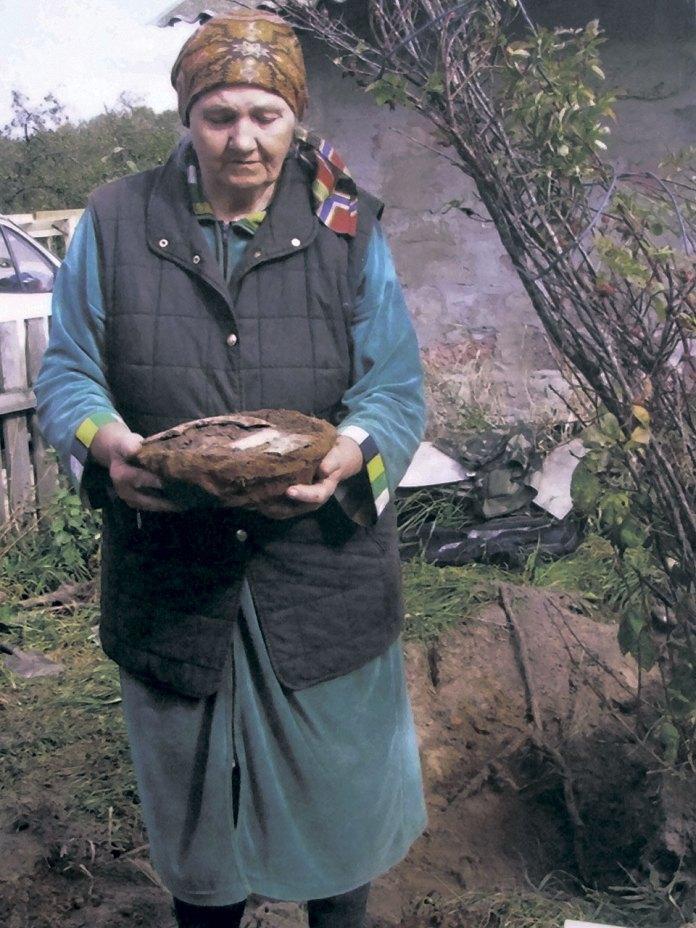 Ганна Тихонівська тримає миску зі спаленими рештками 36 жертв – своєї родини і сусідів, що загинули від Крюківської трагедії