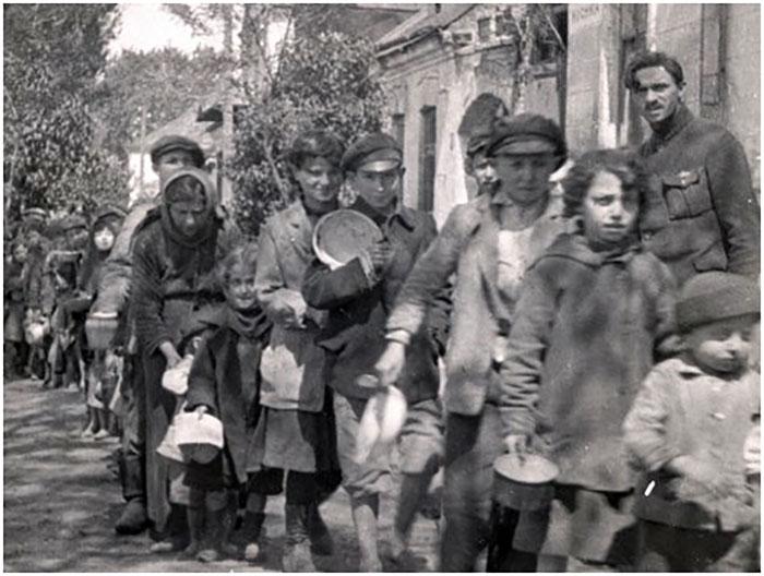 Львівські сироти стоять в черзі за порцією їжі. В руках кожен тримає миску, очікуючи якнайшвидше отримати свій пайок. Фото 1920-х рр.