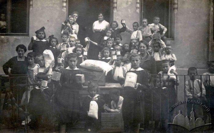 Отримання львівськими дітьми американської гуманітарної допомоги . На фото видно, що діти спеціально позують, тримаючи в руках мішечки з борошном, цукром, банки з какао… Фото 1920-х рр.