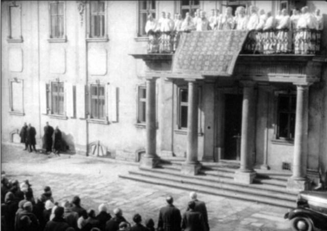 """Митрополит і Іоанн у супроводі єпископів і священиків з балкону архієписькопського дому благословляє вірян, котрі вперше дізнаються про """"самоліквідацію"""" УГКЦ. 10 березня 1946 року"""