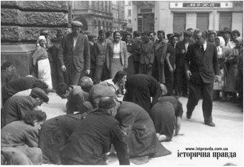 Євреї навколішки чистять територію довкола Оперного театру. Місцеве населення спостерігає з усмішкою на устах.