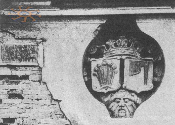 """Герб роду Тарло """"Топор"""" на стіні замку в Мурованому разом з написом, що згадує про відбудову замку в 1561 році."""