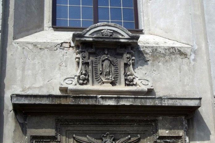 Барельєф Богородиці над дверима бічного фасаду костелу Різдва Пресвятої Богородиці в Комарно