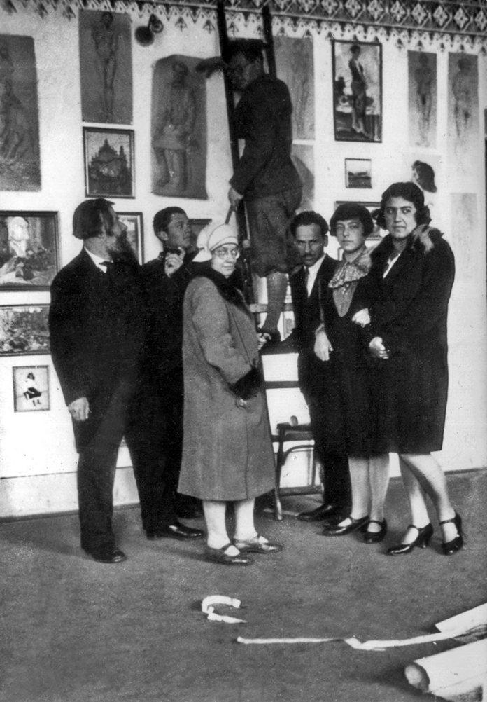 Стефанія Ґебус-Баранецька (друга праворуч) із Олексою Новаківським та іншими вихованцями Мистецької школи під час монтажу звітної виставки, 1928