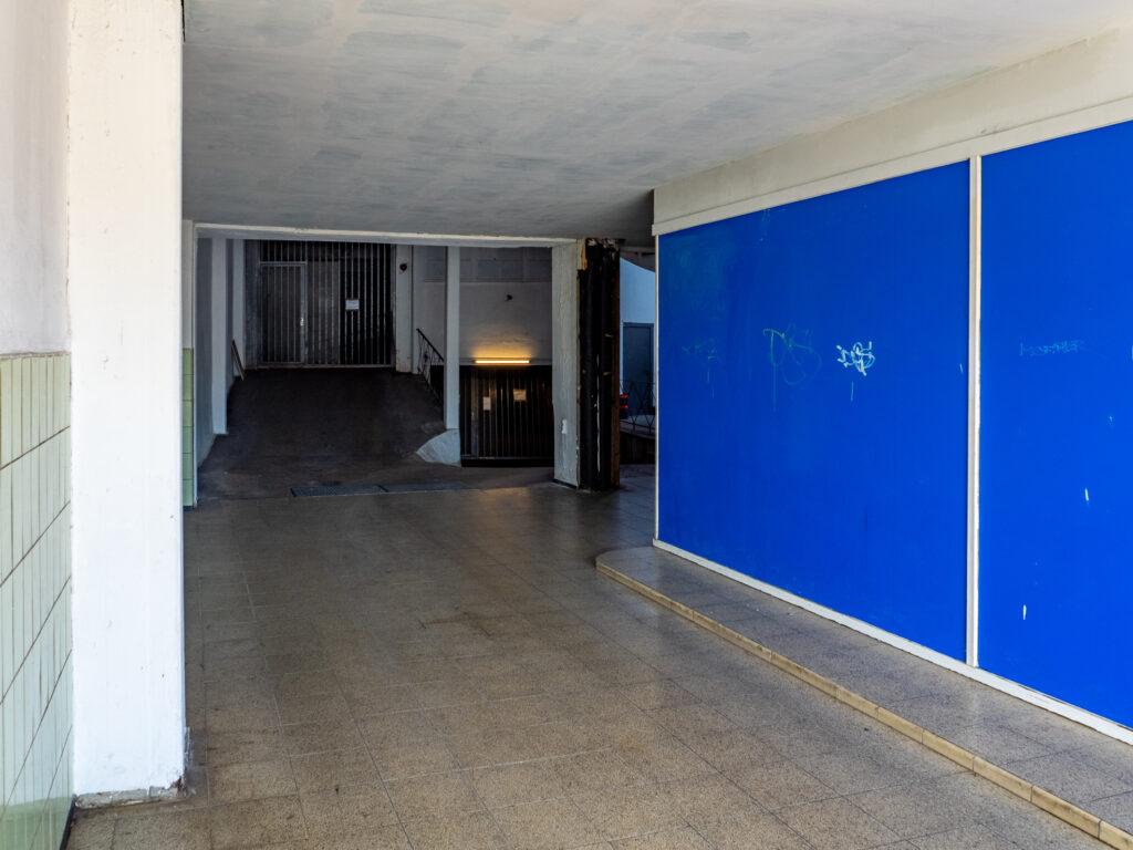 Das Bild zeigt eine Einfahrt mit blauen und grauen Flächen