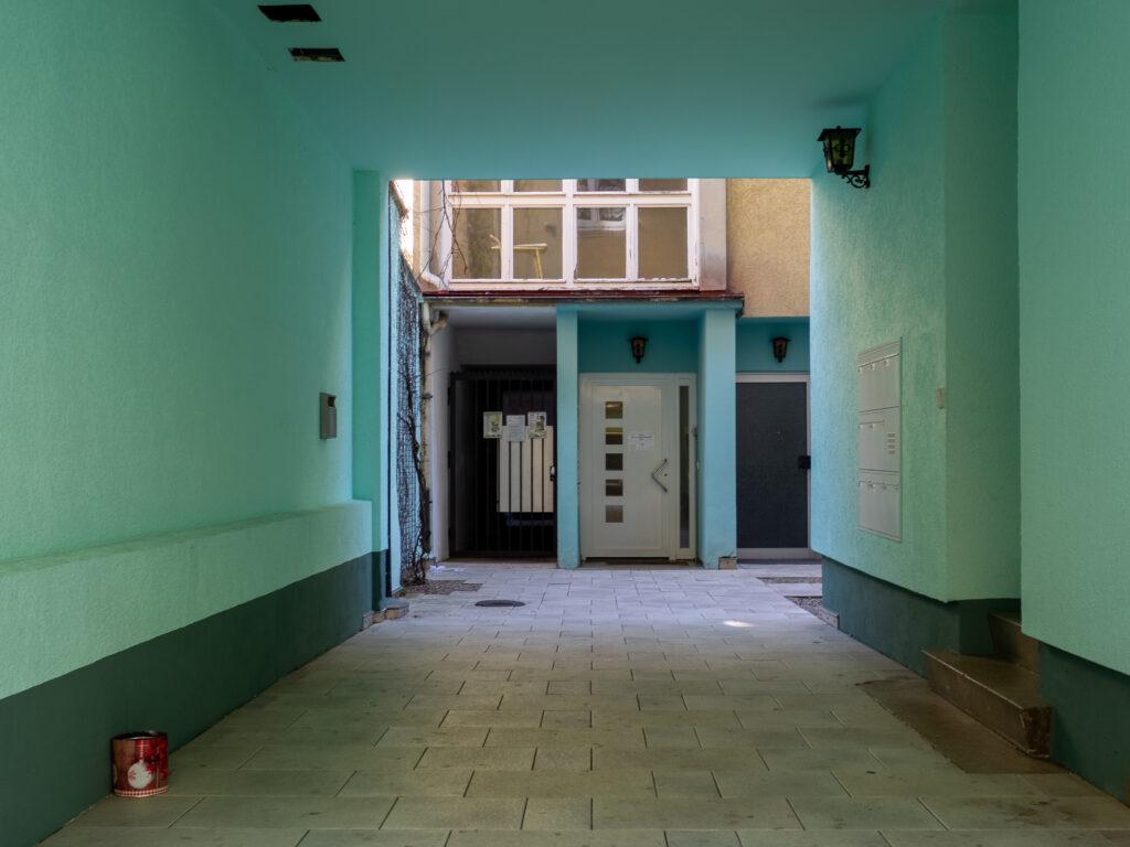 DAs Bild zeigt eine mintgrüne Einfahrt mit eier Tür und dem unteren Teil eines Fensters im Hintergrund.