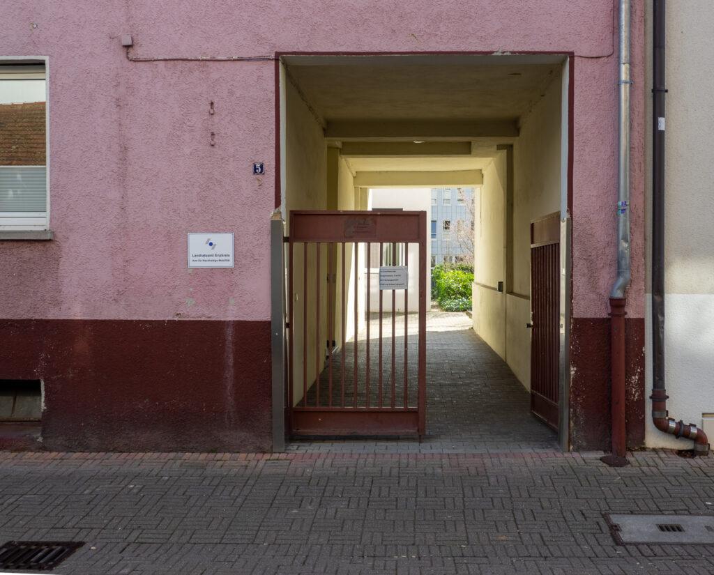Bild zeigt eine Einfahrt mit halboffenen Tor mit brommbeerfarbener Front und gelbem Hintergrund