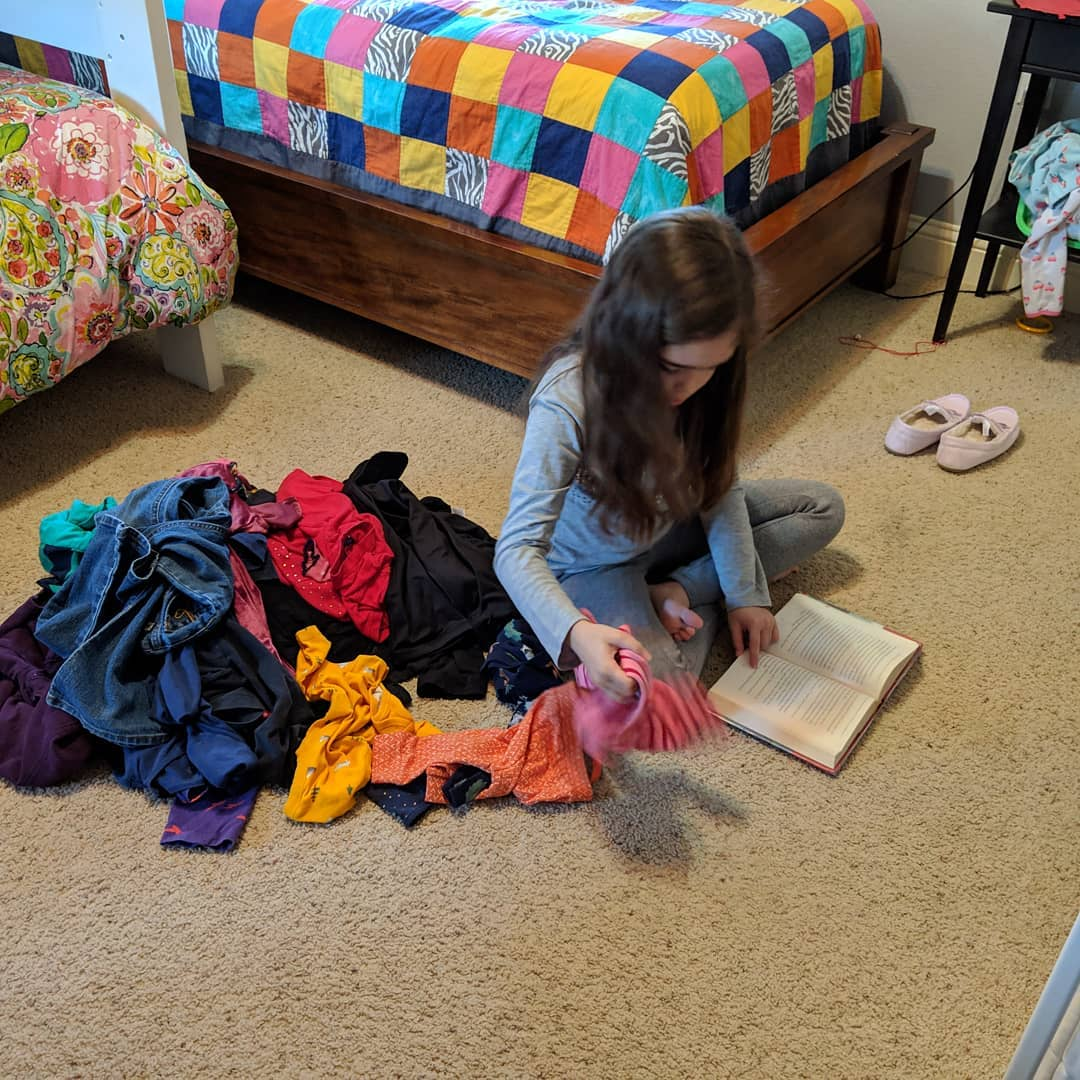 Our bookworm. Reading while sorting clothes
