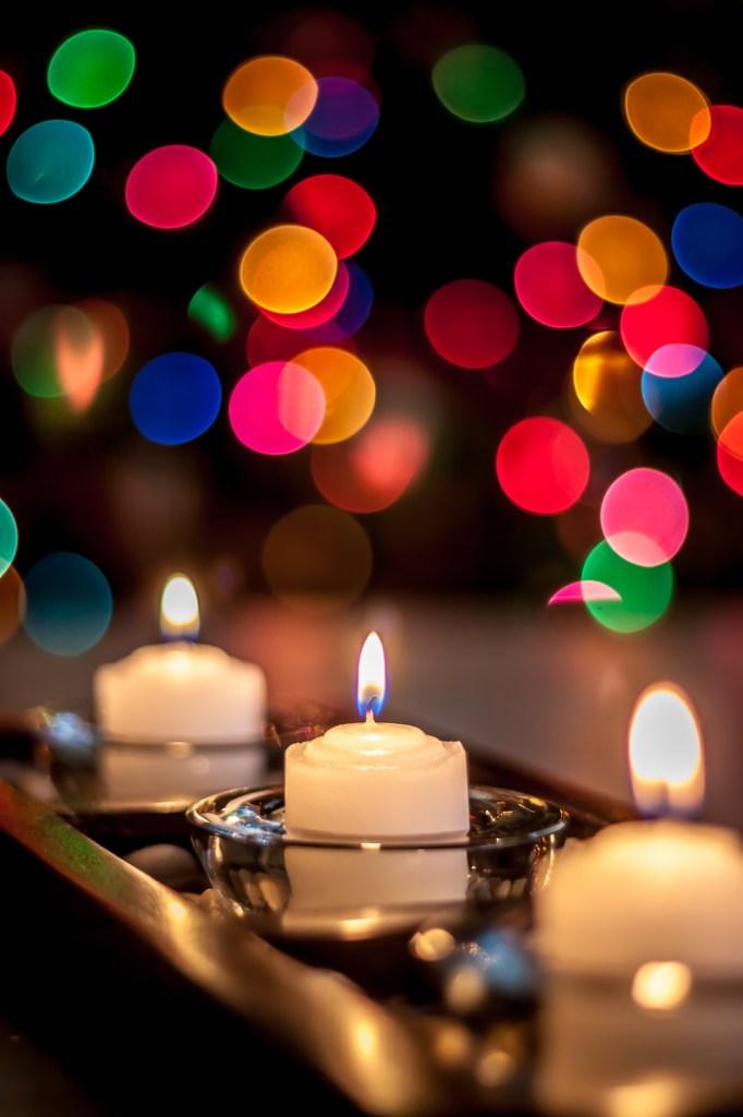 Trois bougies allumées avec des lumières floues multicolores en arrière-plan