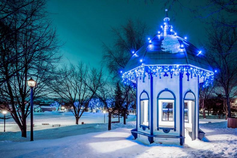 Petit kiosque éclairé de plusieurs lumières bleues avec un ciel aux tons verts