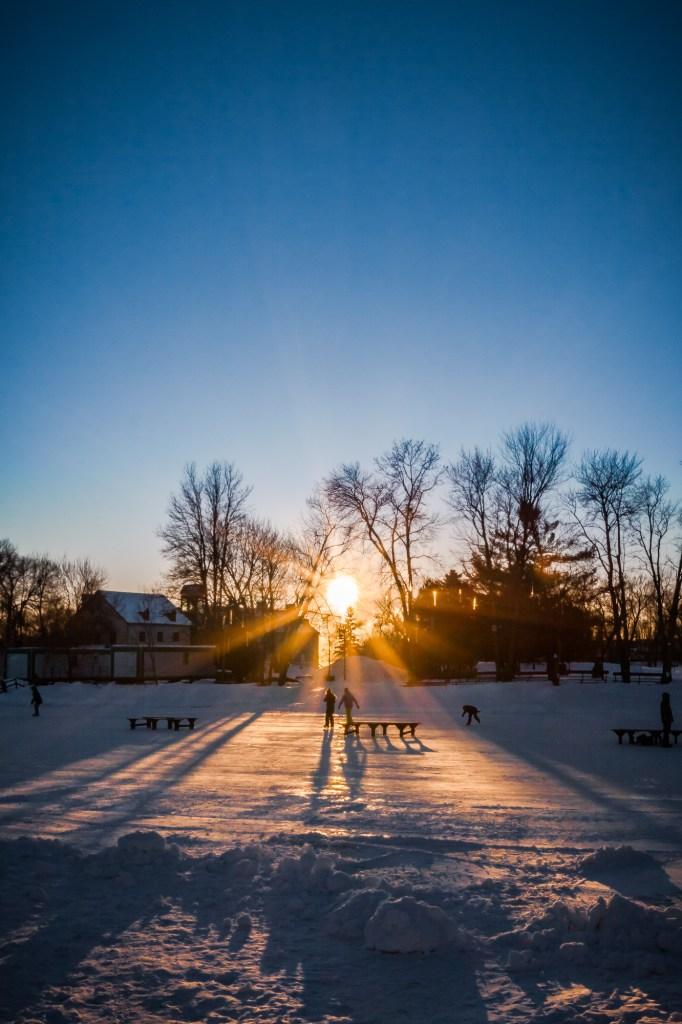 Patineurs sur un étang glacée au coucher du soleil