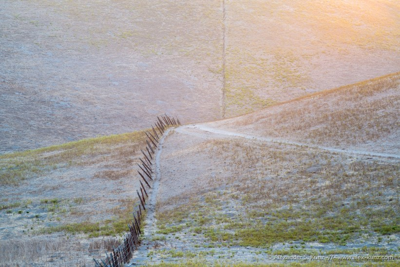 Lines in the landscape: fence, dirt road and slopes