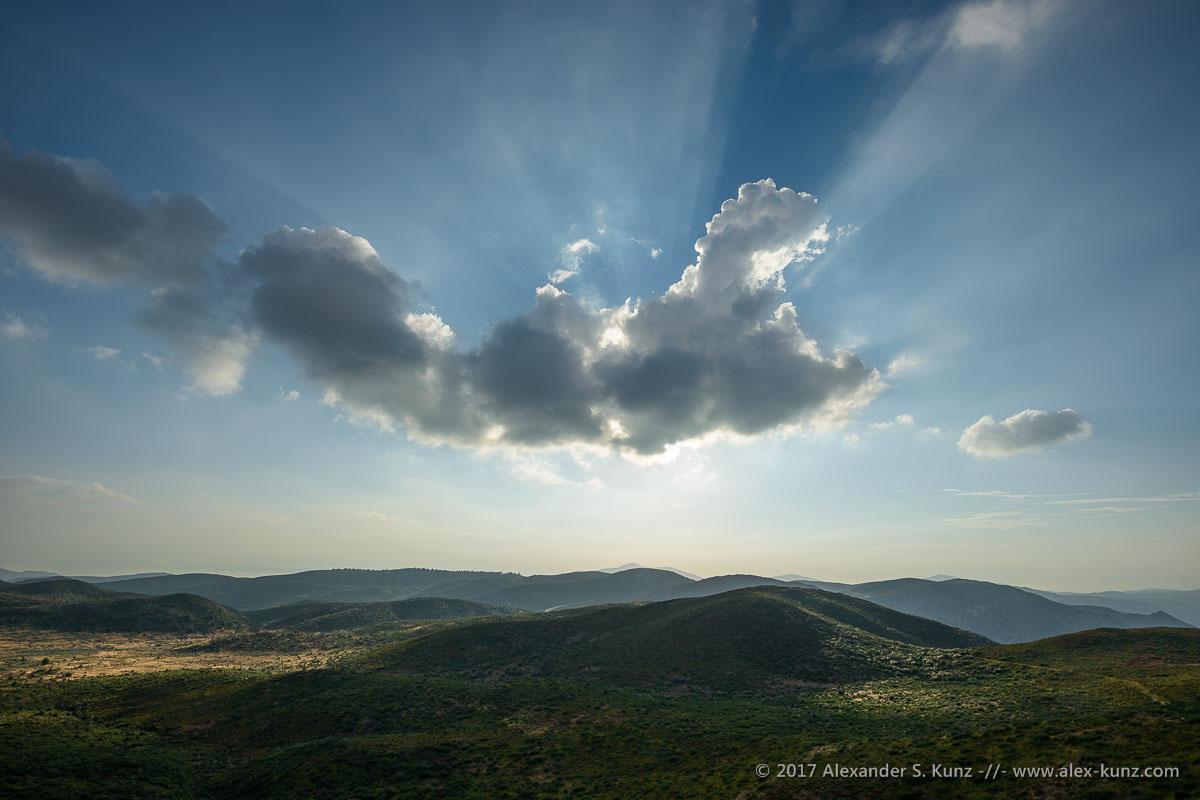 Crepuscular rays shine from behind a cloud hovering over the Laguna Crest, Garnet Peak, Mount Laguna, California