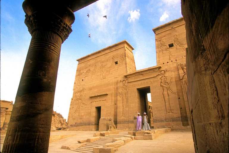 Two Egyptian men talking in front of Edfu Temple in Egypt.