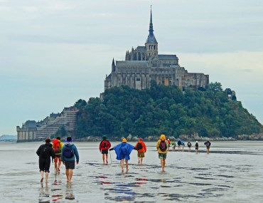 A group of Wilderness Travel clients walks barefoot to Mont Saint Michel in France.