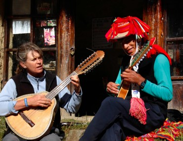 Holly Wissler in the Andean village of Patacancha, Peru, playing the 16-string bandurria with Cristobal Quispe.