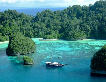 Boat within a cove in the islands of Raja Ampat, Indonesia.