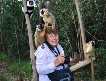 A Wilderness Travel adventurer surrounded by lemurs on Lemur Island, Madagascar.