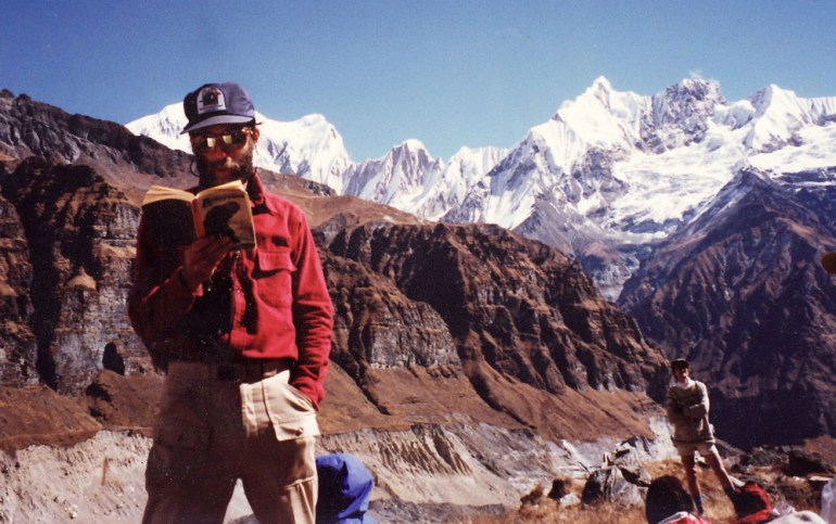 man reading book in everest