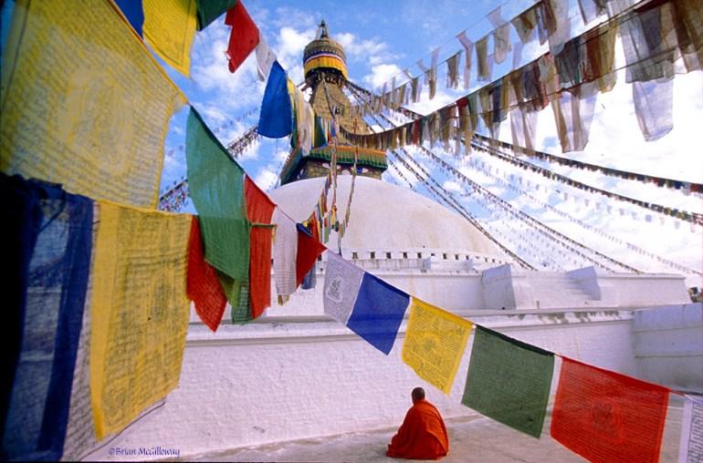 monk meditating in front of bodhnath temple kathmandu nepal