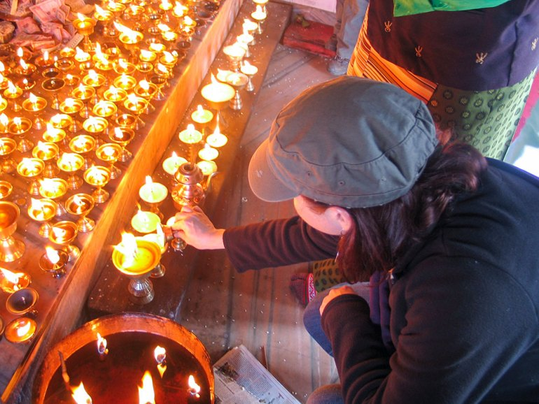 woman lighting candle in temple in Kathmandu Valley Nepal