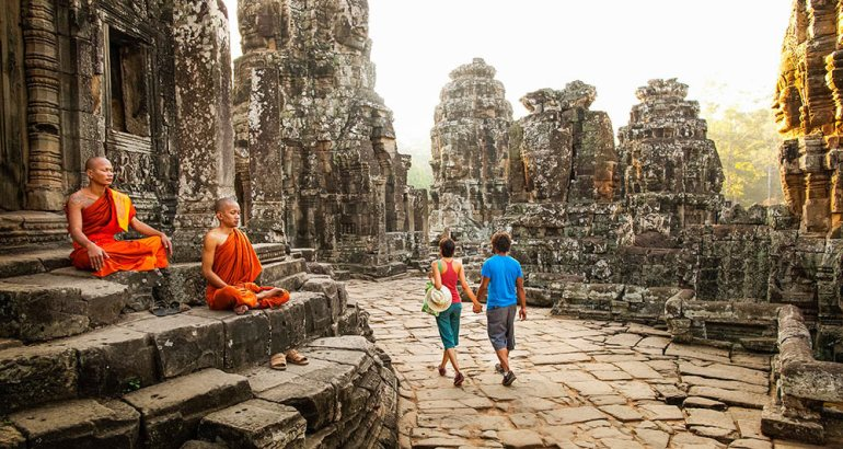 couple walking and monks sitting in siem reap in cambodia